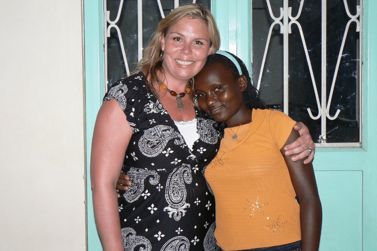 Crisnten poses with a child in Uganda