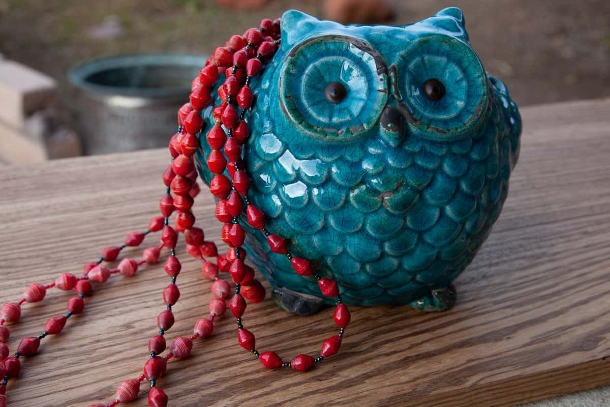 Red beaded necklace and blue owl statue