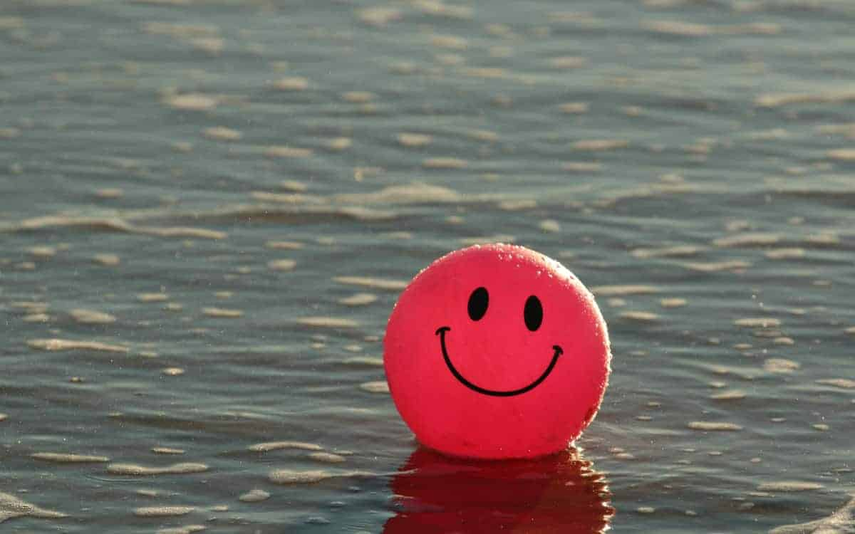 Red happy face ball in water
