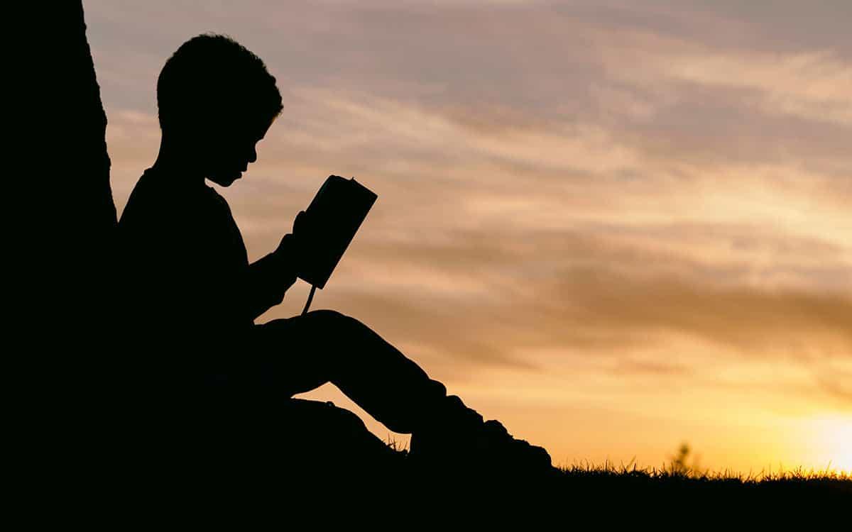 Child reading under a tree.